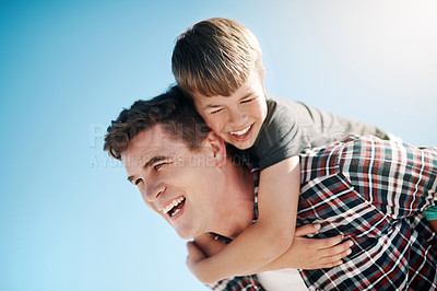 Buy stock photo Shot of a father and his young son enjoying a piggyback ride outdoors