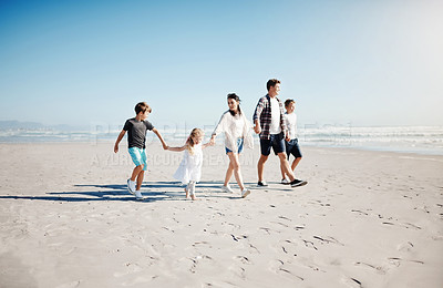 Buy stock photo Shot of a happy young family of five walking together along the beach