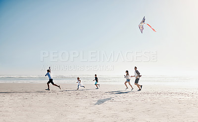 Buy stock photo Shot of a happy young family of five flying a kite together on the beach