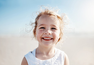 Buy stock photo Portrait of an adorable little girl enjoying a day at the beach