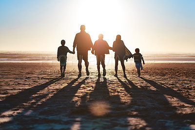 Buy stock photo Rearview shot of a happy young family going for a walk together along the beach