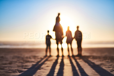 Buy stock photo Blurred shot of a happy young family bonding on the beach at sunset