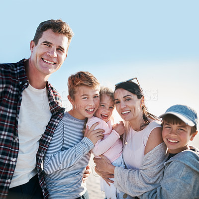Buy stock photo Portrait of a happy young family enjoying a day at the beach