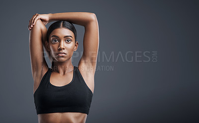 Buy stock photo Studio shot of a sporty young woman stretching her arms against a grey background