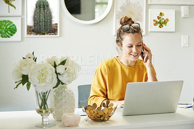 Buy stock photo Shot of a young woman using a mobile phone and laptop while working from home