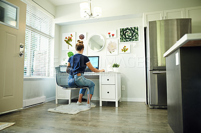 Buy stock photo Rearview shot of a young woman using a computer while working from home