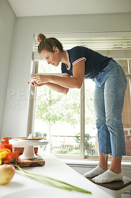 Buy stock photo Shot of a young woman using a mobile phone to take a picture of the pie she's baked at home