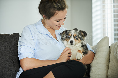 Buy stock photo Shot of a young woman relaxing on the sofa with her dog