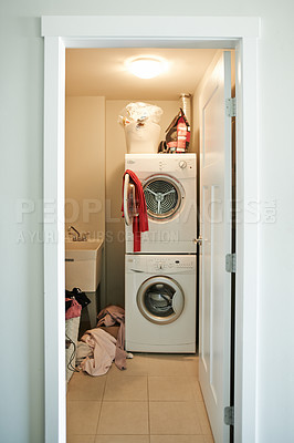 Buy stock photo Shot of a washing machine and dryer in a laundry room at home
