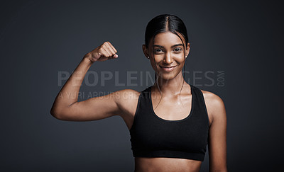 Buy stock photo Studio portrait of a young sportswoman flexing her bicep against a gray background