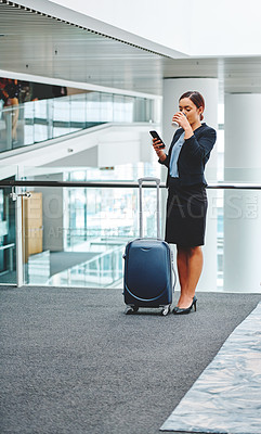 Buy stock photo Full length shot of an attractive young businesswoman sending a text message while standing in the airport