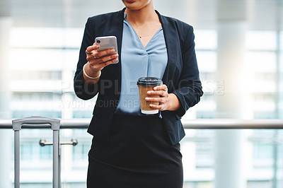 Buy stock photo Cropped shot of an unrecognizable young businesswoman sending a text message while standing in the airport
