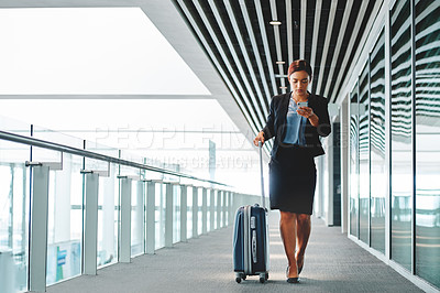 Buy stock photo Full length shot of an attractive young businesswoman sending a text message while walking through the airport