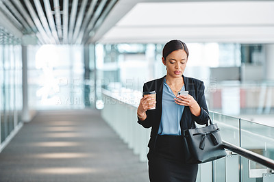 Buy stock photo Cropped shot of an attractive young businesswoman sending a text message while walking through the airport