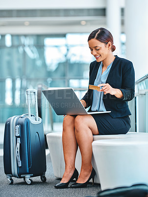 Buy stock photo Full length shot of an attractive young businesswoman using her laptop to shop online while sitting in the airport