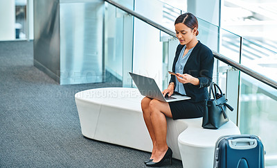 Buy stock photo High angle shot of an attractive young businesswoman using her laptop to shop online while sitting in the airport