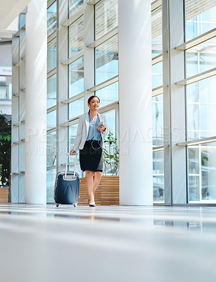 Buy stock photo Low angle shot of an attractive young businesswoman making a phonecall while walking through the airport
