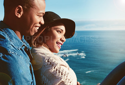 Buy stock photo Shot of a happy young couple enjoying the ocean view on a romantic day outdoors
