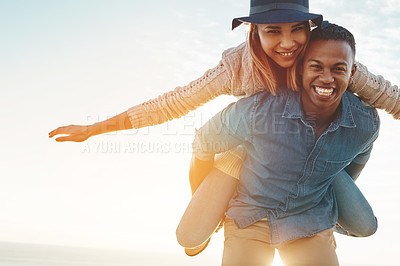 Buy stock photo Shot of a happy young couple enjoying a piggyback ride outdoors