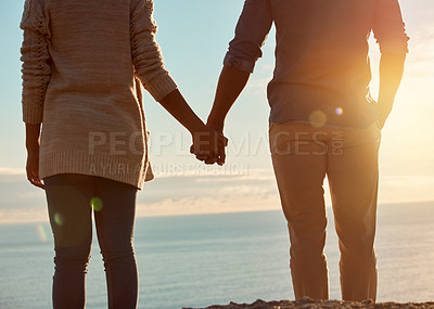 Buy stock photo Rearview shot of a young couple holding hands and overlooking an ocean view