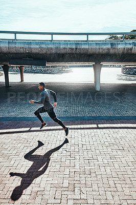 Buy stock photo Full length shot of a handsome and athletic young man running through the city