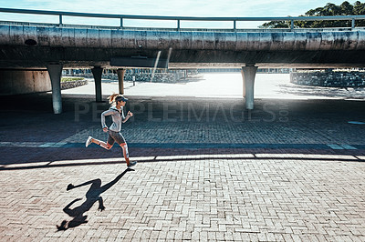 Buy stock photo Full length shot of an attractive and athletic young woman running through the city