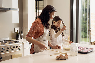 Buy stock photo Shot of a young girl and her mother baking at home