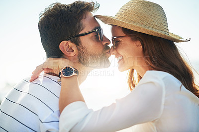 Buy stock photo Cropped shot of a young man kissing his girlfriend's nose on a summer's day outdoors