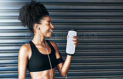 Buy stock photo Shot of a sporty young woman drinking water while exercising against a grey background