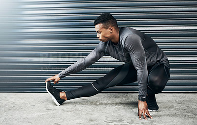 Buy stock photo Shot of a sporty young man stretching his legs against a grey background