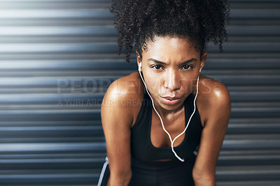 Buy stock photo Portrait of a sporty young woman taking a break while exercising against a grey background
