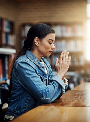 Buy stock photo Cropped shot of an attractive young woman praying for help with her upcoming university exams