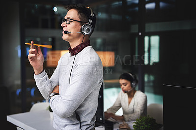 Buy stock photo Cropped shot of a handsome young businessman working late in a call center