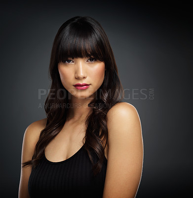 Buy stock photo Studio shot of a beautiful young woman posing against a black background