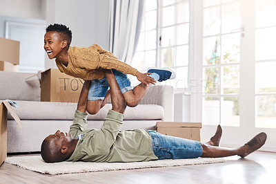 Buy stock photo Shot of a father and his little son having fun while moving house