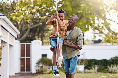 Buy stock photo Shot of a father and his little son playing on a rope swing outdoors