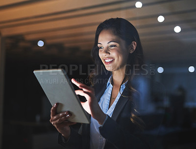 Buy stock photo Cropped shot of an attractive young businesswoman using her tablet while working late in the office