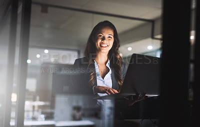 Buy stock photo Cropped portrait of an attractive young businesswoman using her laptop while working late in the office