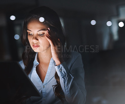 Buy stock photo Cropped shot of an attractive young businesswoman looking stressed while working on her tablet late in the office