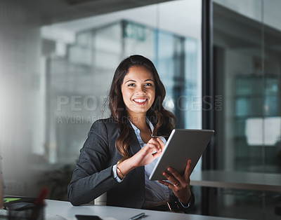 Buy stock photo Cropped portrait of an attractive young businesswoman using her tablet while working late in the office