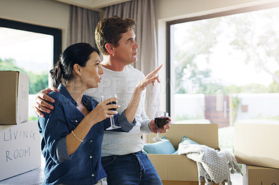 Buy stock photo Shot of a young couple drinking wine together while taking a break from unpacking