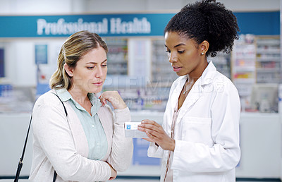 Buy stock photo Shot of a young pharmacist recommending a health care product to a young woman at a pharmacy