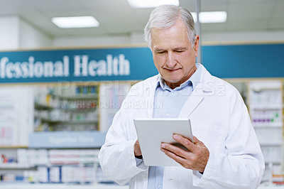 Buy stock photo Shot of a senior male pharmacist doing some work on his digital tablet
