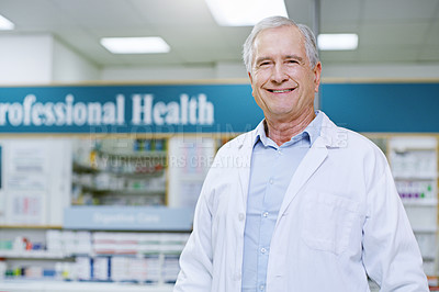 Buy stock photo Portrait of a senior male pharmacist smiling and posing in a pharmacy