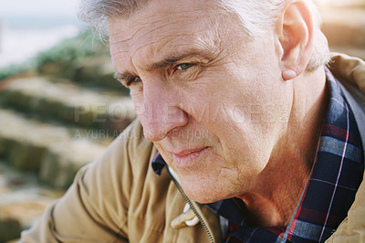 Buy stock photo Closeup shot of an elderly man looking thoughtful while relaxing outdoors