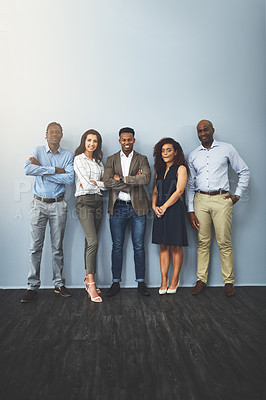 Buy stock photo Studio shot of a group of businesspeople standing together against a gray background