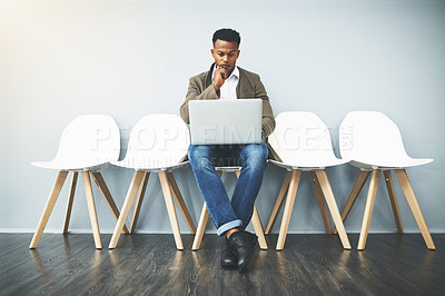 Buy stock photo Studio shot of a young businessman using a laptop while waiting against a gray background
