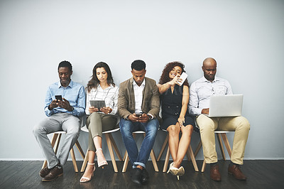 Buy stock photo Studio shot of a group of businesspeople using their wireless devices while waiting in line