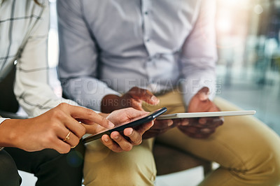 Buy stock photo Closeup shot of two businesspeople using digital devices in synchronicity in an office