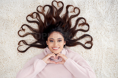 Buy stock photo High angle portrait of a young woman lying on her living room floor with hearts in her hair